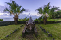 Sunset on coastline of Reunion Island. With old barrel Stock Images