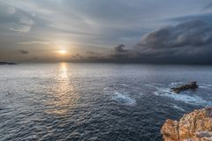 Sunset on the coasts of asturias, spain!. Sunset on the coasts of asturias, spain, semi-hidden the sun among the clouds playing with the natural and beautiful stock photography