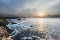 Sunset on the coasts of Galicia, spain!. Sunset on the coasts of Galicia, spain, semi-hidden the sun among the clouds playing with the natural and beautiful royalty free stock image