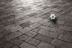 Sunset on cobblestone with soccer ball Royalty Free Stock Photo