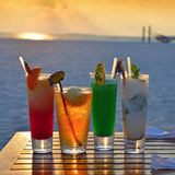 Sunset and cocktails. Beautiful Maldivian sunset and different cocktails on the table near a beach Royalty Free Stock Image