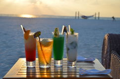 Sunset and cocktails. Beautiful Maldivian sunset and different cocktails on the table near a beach Royalty Free Stock Photo