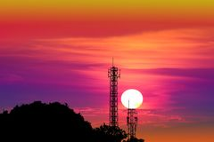 Sunset on colorful evening sky and silhouette signal pole. And mountain stock photography