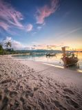 Sunset with colorful sky and boat on the beach Stock Images
