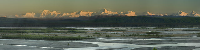 Sunset colors of the early summer Alaska Range. Warm evening colors of the polar night in Alaska. Visible are mt. Debra and mt. Hess. Meandering river in Stock Photos