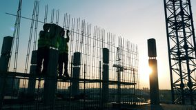 Sunset construction site with builders assemblying metal carcass. 4K stock video