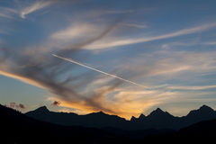 Sunset and contrail over mountains Stock Photography