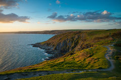 Sunset on Cornish cliffs, ocean and foot patch in wild scenery Stock Photo