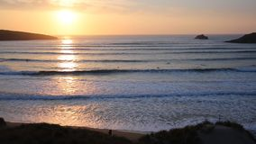 Sunset in Cornwall with surfers surfing Crantock near Newquay UK stock video