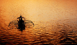 Sunset at Coron Port. The sunset silhouettes a traditional fishing boat in Coron Bay, Palawan royalty free stock images