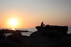 Sunset in Corsica. Backlighted woman on rocks in front of a sunset over the sea Royalty Free Stock Photos