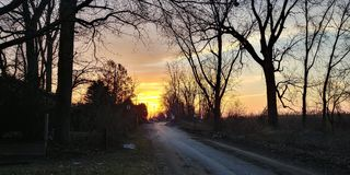 Sunset country road. Sunset down a country road next to marsh Stock Photos