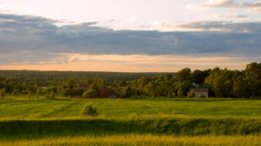 Sunset in countryside. View of northern russian small village at sunset Royalty Free Stock Photography