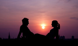 Sunset couple. Silhouette couple sitting at sunset Royalty Free Stock Photography