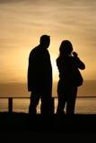 Sunset couple. Looking the sea Stock Photo