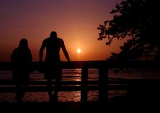Sunset Couple. A couple standing on a pier watching a sunset Stock Image