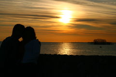 Sunset with couple. A dramatic sunset in Bright with silhouettes of two people hugging royalty free stock photography