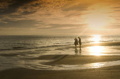 Sunset couple on the beach. Sunset at the beach with two people relaxing Stock Images
