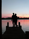 Sunset Couple on Pier. A gorgeous sunset with a couple silhouetted at the end of a pier Stock Photos