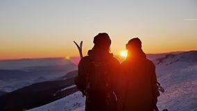Sunset Couple Winter People Ski Slowmotion. Slowmotion footage of a skier and snowboarder admiring a beautiful sunset stock footage