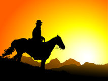 Sunset Cowboy. Cowboy and his horse silhouettes against a sunset royalty free illustration