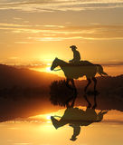 Sunset cowboy by a lake in the mountains. A cowboy rides his horse into the sunset with clouds along a lake with his reflection in the water after a long day of Stock Photo