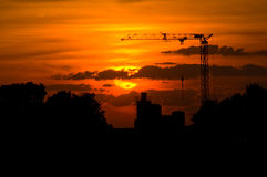 Sunset crane. Sunset with a silhouette of a crane and factory in the back Royalty Free Stock Photo