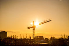 Sunset through a crane in industrialized area of city Royalty Free Stock Photos