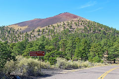 Sunset Crater volcano cinder cone near Flagstaff, Arizona. Sign and slope of the cinder cone at Sunset Crater Volcano National Monument north of Flagstaff Royalty Free Stock Images