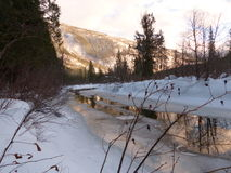 Sunset creek 1. A serene winter scene.Clear cold water,mountains and snow.Sunlight reflected in the water,blue sky`s Royalty Free Stock Photos