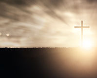 Sunset Cross. A Christian cross at sunset with light flares royalty free stock images