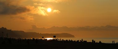 Sunset on the crowded beach. Cloudy weather over Baltic sea Royalty Free Stock Photos
