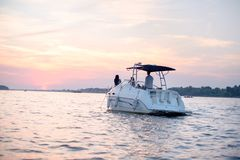 Sunset cruise, boat with people. Boat with young people cruising in sunset with a beautiful sky stock image
