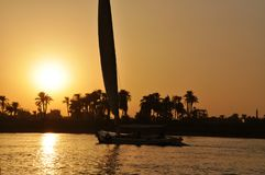 Boat sailing on the Nile river at sunset, Luxor, Egyptian. In the sunset at the cruise of the Nile River, felluca boat, Luxor, Egypt Stock Image