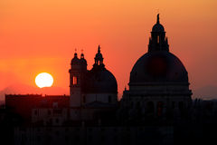 Sunset and cupola of a church. Orange sunset and the dark outlines of a venetian cathedral Royalty Free Stock Image