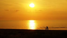 Sunset over sea and sport bike Stock Images