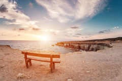 Sunset in Cyprus - Mediterranean Sea coast. Sea Caves near Ayia Napa. the bench in the background of space. you can sit Royalty Free Stock Photo