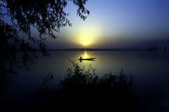 Sunset Dal Lake. Sun sets on the Dal Lake in Kashmir as a man paddles his boat away to shore Stock Photography
