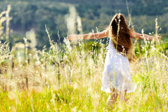Sunset dancing meadow girl. Beautiful girl laughs and dances outdoors in a meadow durning sunset Royalty Free Stock Photography