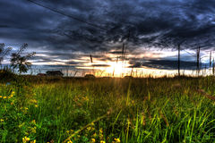 Sunset. With dark clouds, orange sky and green grass Royalty Free Stock Photography