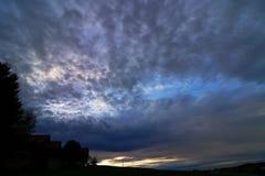 A sunset with dark rain clouds Stock Photos