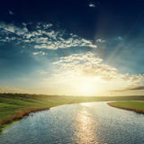 Sunset in dark sky over river Royalty Free Stock Photos