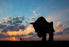 Sunset dawn sun rays over the city sky field statue bison sculpture silhouette family walking near the sun stock photography