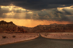 Sunset in desert. Beautiful cloudy evening sky over narrow road running towards mountains of Arava desert in Israel Royalty Free Stock Photos