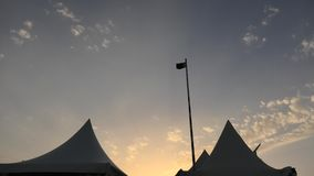 Sunset in desert camp. Sunset in a desert camp with tents of Qatar, Khor Al Udeid, Persian Gulf, Middle East. Flag of Qatar waving high in the sunset sky with stock video
