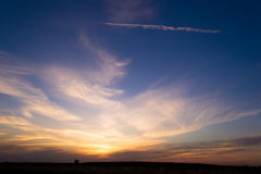 Sunset in the desert. Summer prairie sunset, which left a trace of the aircraft flown by Stock Photography