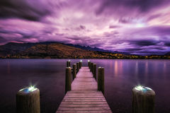 Sunset with a dock in lake wakatipu. Sunset over lake wakatipu with kelvin heights in the distance. Sunlight covered in stormy clouds. Taken during summer. Small Stock Image