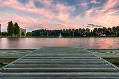 Sunset from a dock over a lake. Sunset over a beautiful lake in Rotterdam with a fountain in the background Stock Photography