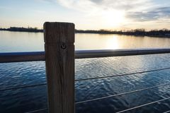 Sunset from dock railing by water Stock Photography