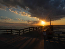 Sunset at the docks. With clouds.  Burst of lights stream across the docks Stock Image